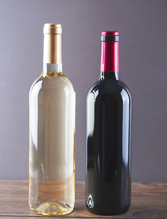 unmarked: Vertical studio shot of two unmarked bottles for red and white wine on wooden table. Stock Photo
