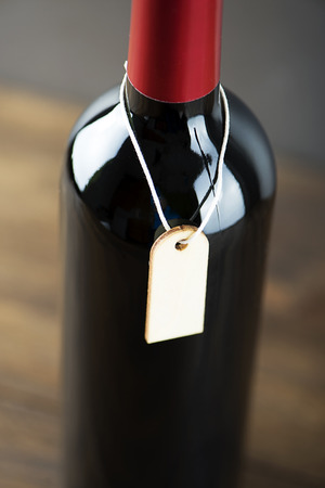 Close-up of red wine bottle with a sign around on gray background. Mockup. Vertical studio shot. Stock Photo