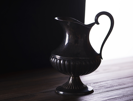 antique vase: Metal decoration jug on wooden table and black and white background. Backlighting.