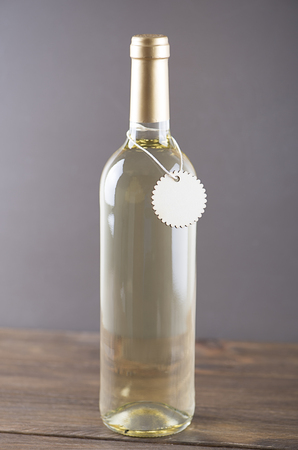 White wine bottle with a sign around on gray background. Mockup. Vertical studio shot.