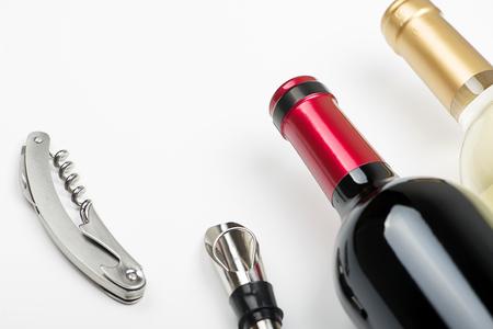 Top view of corkscrew on white background next to several corks. Horizontal studio shot. Isolated. Stock Photo