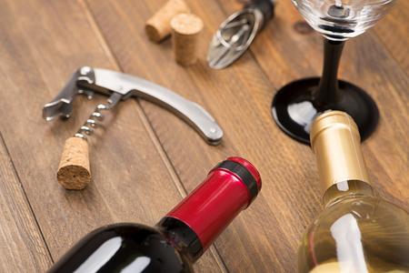 栓抜きワインと木製のテーブルにガラスの 2 つのボトルの横にあります。水平のスタジオ撮影します。