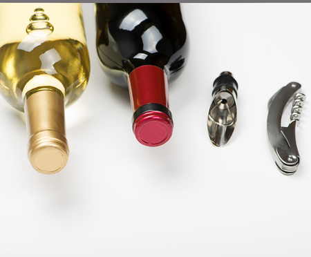Corkscrew next to two bottles of white wine on white background. Isolated. Vertical studio shoot.