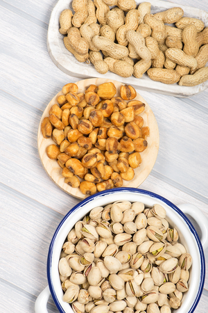 Peanuts, pistachios and toasted corn on wooden background. Vetical studio shot. Stock Photo