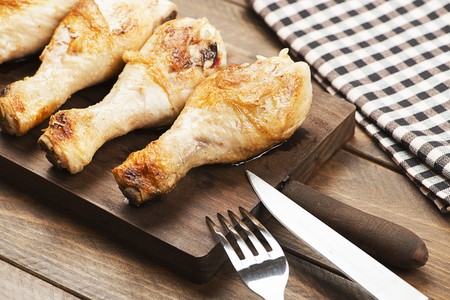 Roasted chicken on board next to napkin, knife and fork. Stock Photo