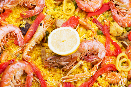 containing: From above big paella dish containing shrimps and rice with vegetables.
