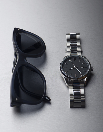 Dark sunglasses next to metallic clock on gray background. Vertical studio shot.