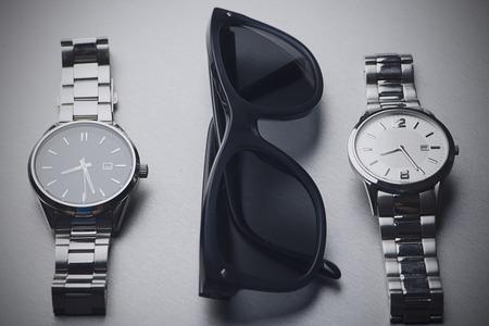 Dark sunglasses next to two metal watches on gray background. Horizontal studio shot.