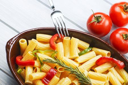 Close-up vista de tazón con pasta de verduras servido en la mesa con tomates frescos y un tenedor.