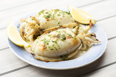 Cuttlefish with garlic and parsley next to lemon. Food. Stock Photo