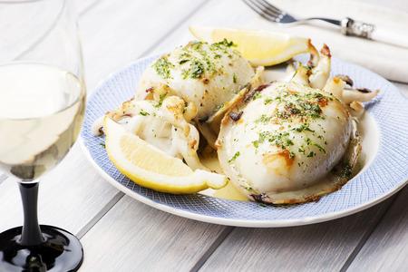 Inktvis Met knoflook, peterselie en citroen naast een glas wijn, vork en servet. Eten. Stockfoto