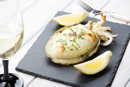 Cuttlefish with garlic and parsley, lemon next to white wine glass on whiteboard. Food.