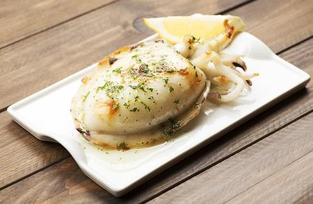 마늘과 파 슬 리와 레몬 나무 테이블에 오징어의 근접. 스톡 콘텐츠