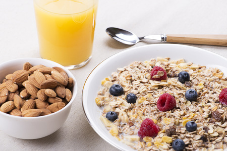 Cereal bowl breakfast with milk, raspberries and blueberries next to orange juice and bowl with almonds.