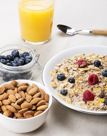 Cereal bowl breakfast with milk, raspberries and blueberries next to orange juice and bowl with almonds. Vertical studio shot. Stock Photo