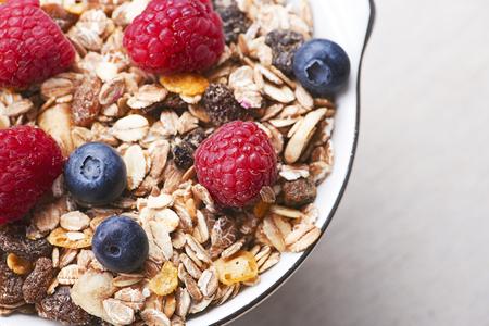 朝食のシリアルにラズベリーとブルーベリーのクローズ アップ。領域をコピーします。