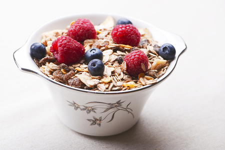 Breakfast cereal with raspberries and blueberries.