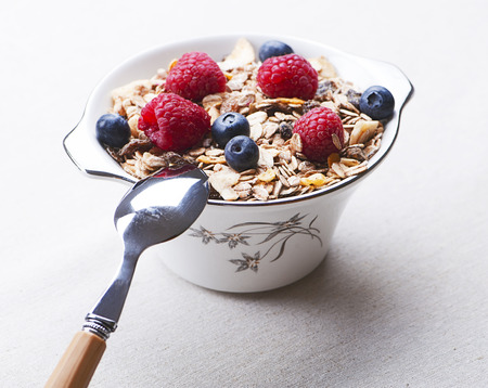 Breakfast cereal with raspberries and blueberries next to spoon.