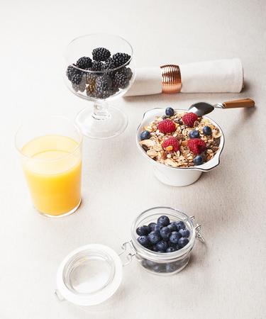 Breakfast cereal with raspberries and blueberries along with orange juice and tasty blackberries. Vertical studio shot.