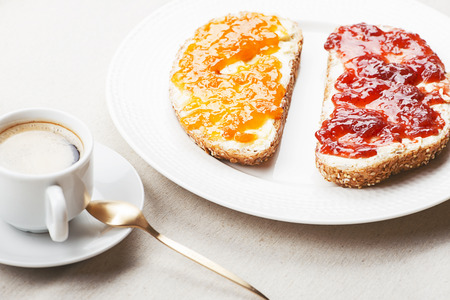 Toast with marmalade next to a cup of coffee on a tablecloth.