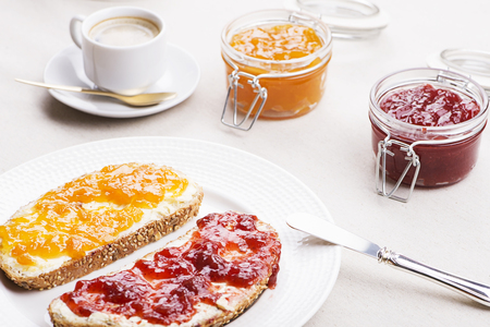 Two toasts with strawberry jam and peach next to cup of coffee on tablecloth.