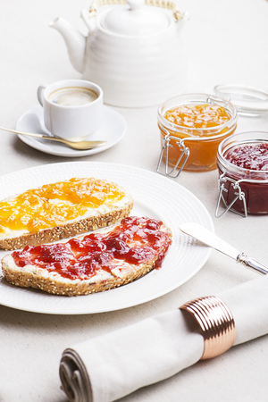 Two toasts with strawberry jam and peach next to cup of coffee on tablecloth. Vertical studio shot. Stock Photo