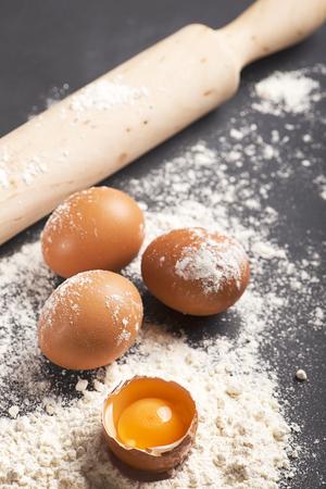 Eggs on flour next to wooden roller on black wooden table. Vertical studio shot.