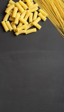 マカロニと黒い背景にスパゲッティ。領域をコピーします。垂直のスタジオ撮影します。