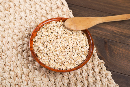 Bowl with oats next to wooden spoon on wooden table. Closeup Stok Fotoğraf