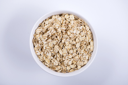 Top view of white bowl with oats on white background. Isolated.