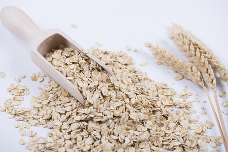 Oat flakes next to wooden spoon on white background. Isolated.