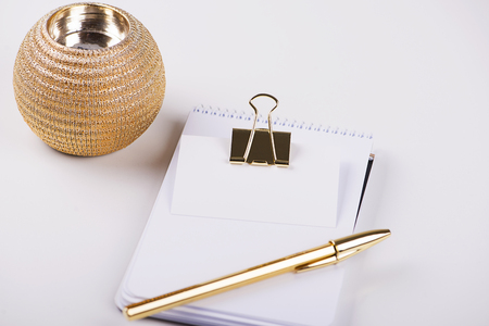 Notepad with blank paper next to golden ball pen and business card with golden clip on white background. Isolated. Decor. Mockup.