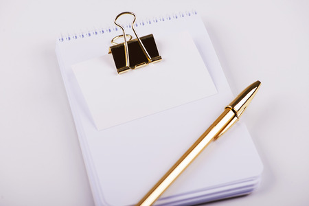 Notepad with blank paper next to golden ball pen and business card with golden clip on white background. Isolated. Mockup.