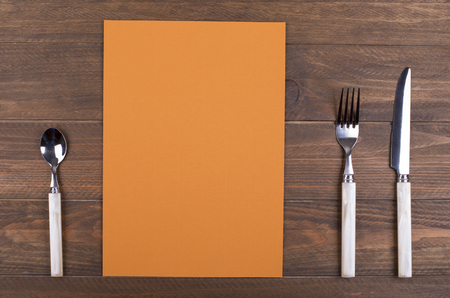 Empty orange paper between covered kitchen on wooden table. Menu. Food