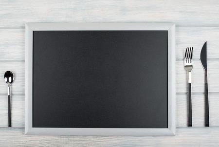 Blackboard between covered kitchen on wooden table. Menu. Food