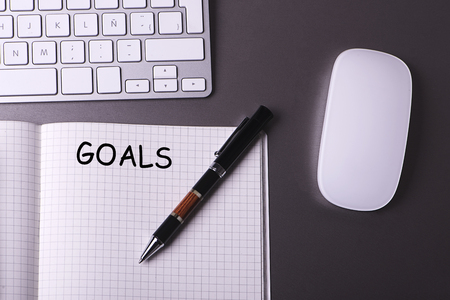Concept of workplace with keyboard, mouse, pen and notepad with the word Goals written on it. Stock Photo