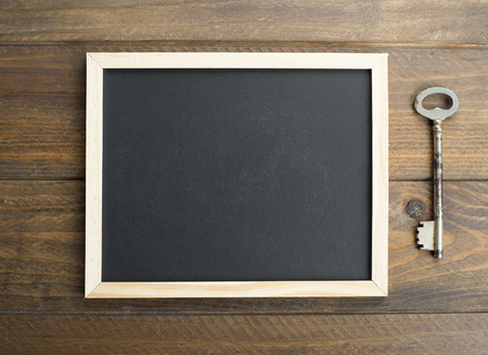 Top view of chalkboard next to old key on brown wooden table. Copy space. Stock Photo