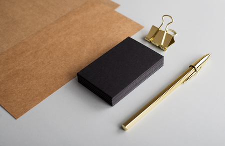 Top view of brown cards and business card of black color next to clip and golden ball pen on gray background. Mockup.