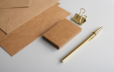 Top view of cards, envelope, business card in brown color with clip and golden ball pen on gray background. Mockup.