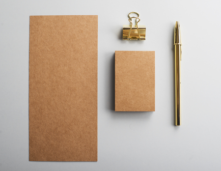 Brown cardboard and business card of brown color next to clip and golden ball pen on gray background. Mockup.