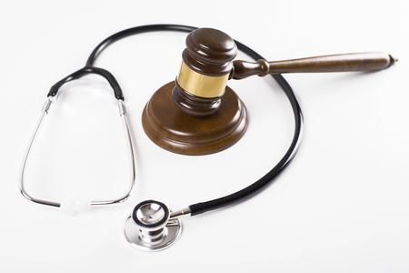 Judge gavel next to stethoscope on white background. Isolated. Medical negligence concept. Stock Photo
