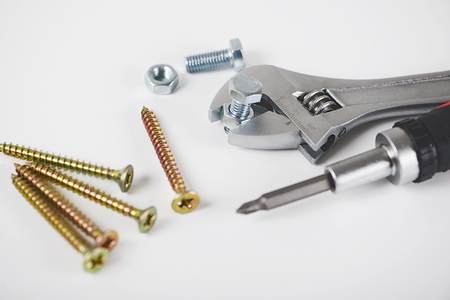 Close-up of spanner, screwdriver, nuts and bolts isolated on a white background. Industrial concept