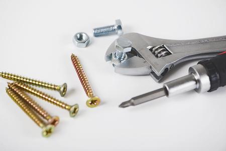 Nahaufnahme von Schraubenschlüssel, Schraubendreher, Muttern und Bolzen lokalisiert auf einem weißen Hintergrund. Industrielles Konzept