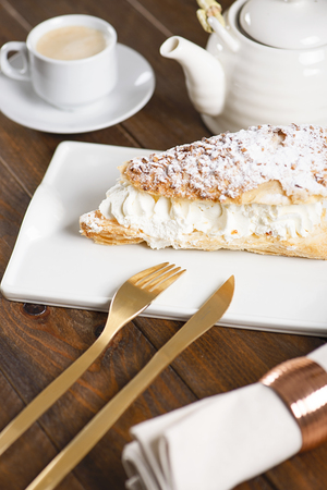 Delicious breakfast of coffee with puff pastry with cream. Vertical shoot. Food Stock Photo