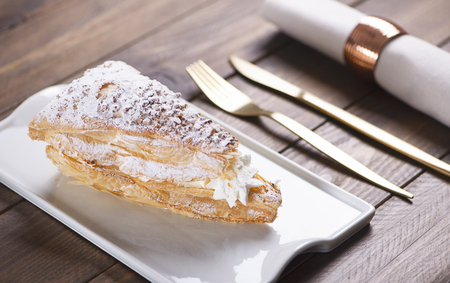 Close-up of delicious breakfast of sweet puff pastry with cream on brown wooden table. Horizontal shoot. Food 版權商用圖片
