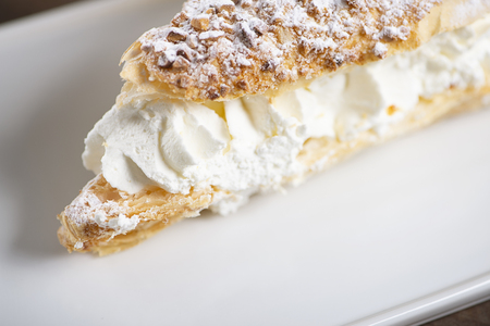 Close-up of delicious sweet puff pastry with cream on white plate.