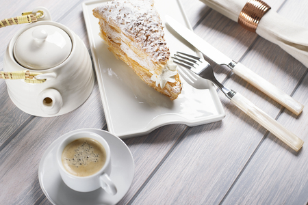 Delicious breakfast of coffee with puff pastry with cream on wooden table. Horizontal shoot. Food Stock Photo