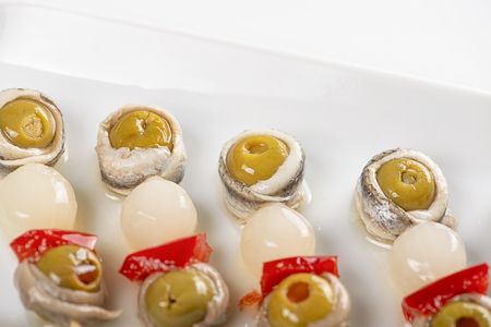 Banderillas of olives with spring onion and anchovies on a white plate. Isolated. Typical spanish food. Stock Photo