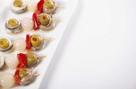 Olives banderillas with chives and achoas on a white plate. Isolated. Typical spanish food. Copy space. 免版税图像