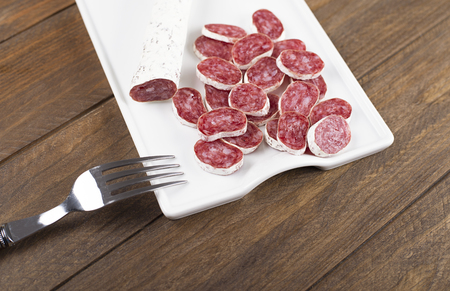 Sausage called fuet on white plate. Typical spanish food.